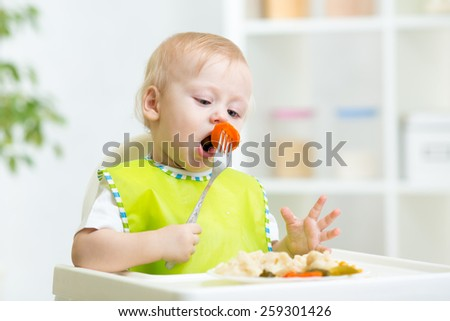 toddler boy in a highchair for feeding with a fork and a plate indoor - stock photo