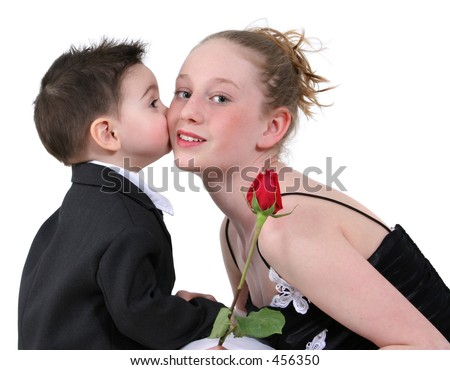 Toddler boy in suit kissing a beautiful teen girl on the cheek. - stock photo