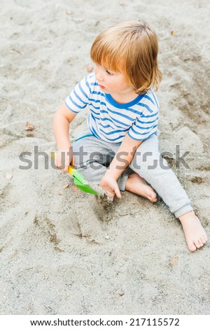 Toddler boy playing in the sandbox - stock photo