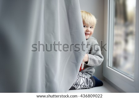 Toddler boy playing on the window sill at home - stock photo