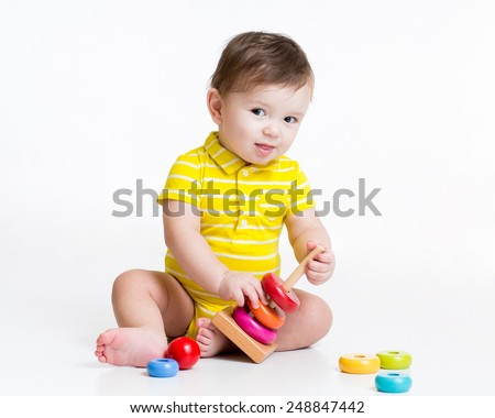 toddler boy playing with colorful toy pyramid - stock photo