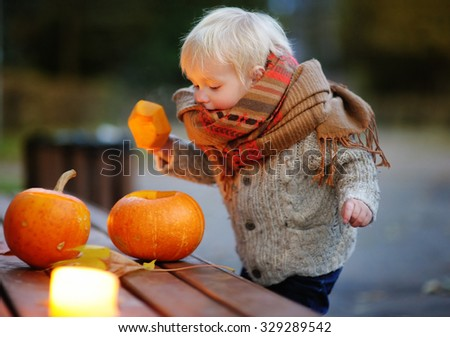 Toddler boy playing with halloween pumpkins, halloween party - stock photo