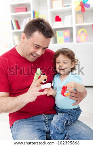 Toddler boy playing with his father at home - stock photo