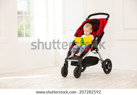 Toddler boy sitting in stroller at home and looking at open book - stock photo