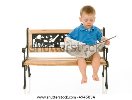 Toddler boy sitting on a park bench and looking down at the newspaper. Isolated on white. Note to buyers and inspectors: Text on newspaper prop is blurry so that no text is legible.