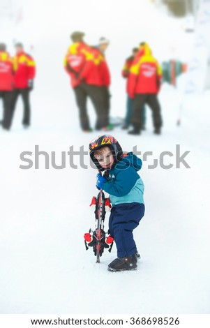 toddler boy skiing in the mountains, winter time