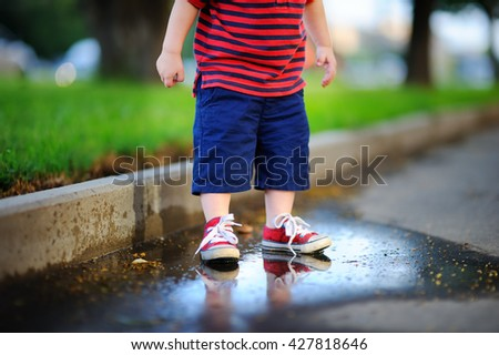 Toddler boy standing in a puddle on a warm summer or autumn day  - stock photo