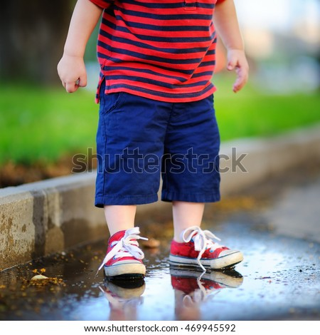 Toddler boy standing in a puddle on a warm summer or autumn day