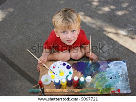 toddler boy with brushes and colors painting - stock photo