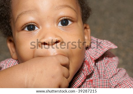 toddler boy with fingers in mouth - stock photo