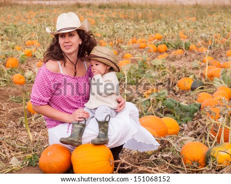 Toddler boy with his mom on the farm.