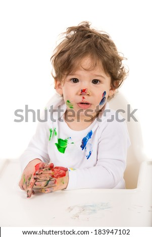 Toddler boy with messy face and hands sitting in a high chiar