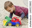 Toddler child boy playing with a plastic toy digger car.  - stock photo