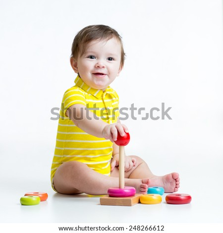 toddler child boy plays with colorful toy pyramid - stock photo