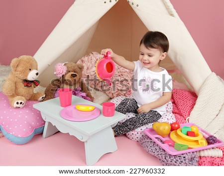 Toddler child, kid, engaged in pretend play with food, stuffed toys, and teepee tent - stock photo