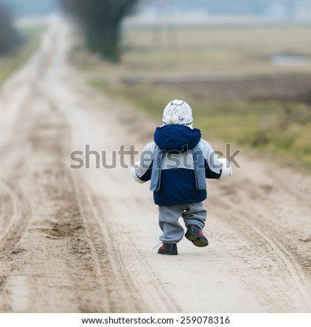 toddler child walking by rural sandy road - stock photo