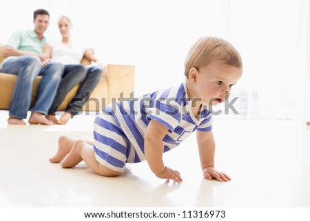 Toddler crawling with parents in background - stock photo