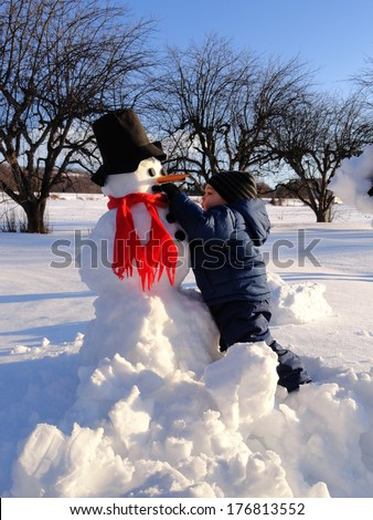 Toddler decorating a snowman - stock photo
