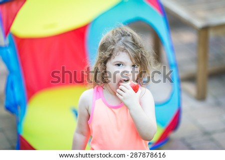Toddler eating an apple outdoors - stock photo