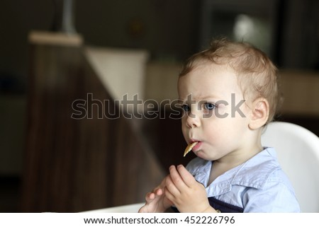 Toddler eating pancake at a dinner table - stock photo
