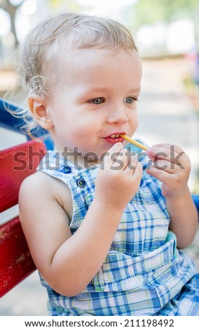 Toddler eating sweet straw sitting on the bench