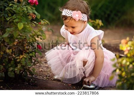 Toddler enjoying roses in the garden - stock photo
