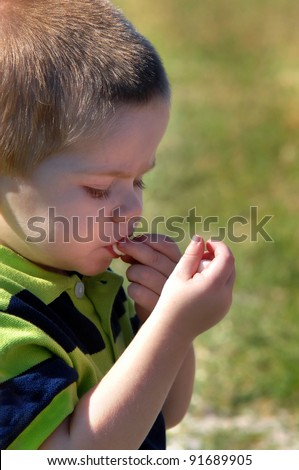 Toddler enjoys his snack of mini marshmallows.  As he puts one in his mouth, he examines the other ones gripped tightly in his other fist. - stock photo