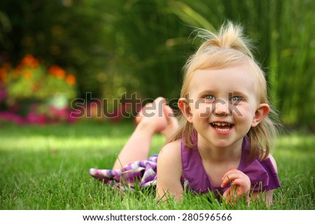 Toddler filled with wonder playing outside - stock photo