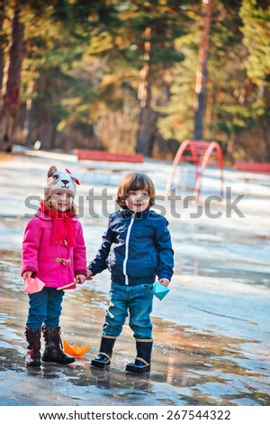toddler friends are happy playing in spring puddle with colorful paper boats - stock photo