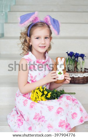 Toddler funny girl with bunny ears at home ready to celebrate spring and Easter with flowers and ginger bread
