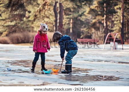 toddler girl and boy plays on the early spring walk with paper boats in melting snow - stock photo