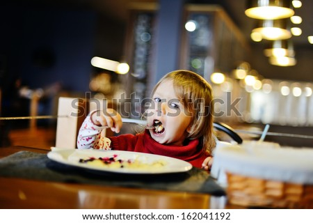 toddler girl eating in restaurant - stock photo