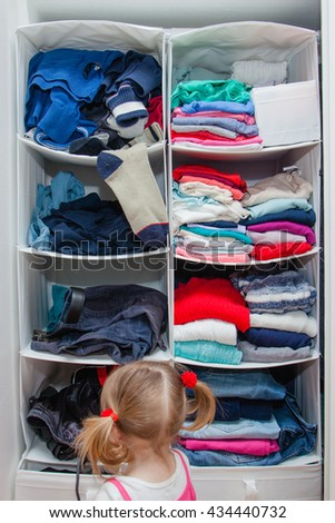 Toddler girl explore wardrobe shelves of her parents. Concept of gender difference: arrangement, color preference, neatness and clutter, order and mess. Childish curiosity.