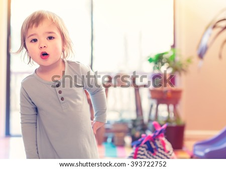 Toddler girl in blue dress in her house - stock photo