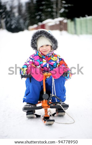 Toddler girl in colorful snowsuit riding her snow scooter