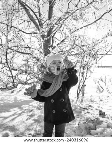 Toddler girl in peacoat and scarf posing by a frost covered tree in winter in black and white