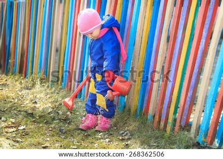 Toddler girl in spring blue overall with pink knitted hat and kids boots is pouring water with watering red plastic can - stock photo