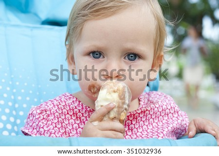 Toddler girl in the pink dress eating ice cream and looking aside.  Happy little girl with blond hair and deep blue eyes has a tasty snack in a hot summer day. Close up portrait. Colorful photo. - stock photo