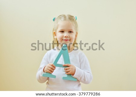 toddler girl is  standing  with letter A - stock photo