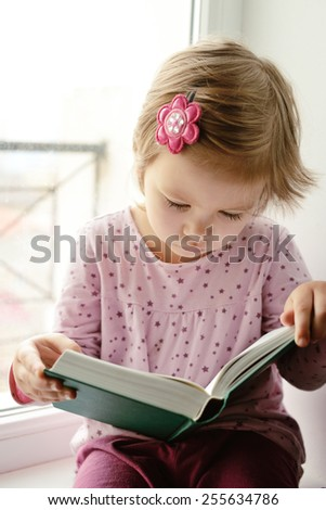 toddler girl is trying to read a book - stock photo