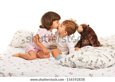 a girl and a boy kissing in bed