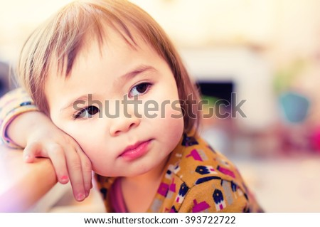 Toddler girl leaning against table in her house - stock photo