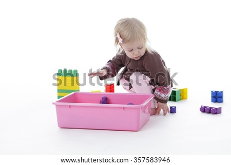 toddler girl picking up toys in pink bin, isolated on white background - stock photo