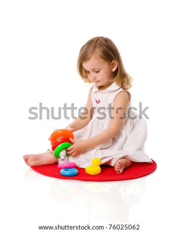 toddler girl playing with pyramid isolated on white