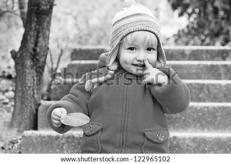 toddler girl pointing her nose and holding leaf in black and white - stock photo