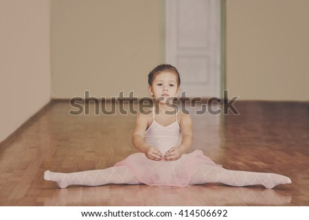 toddler girl sitting in cross split in ballet school
