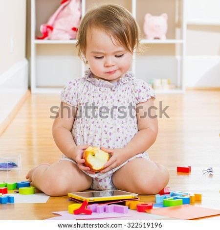 Toddler girl using a tablet computer and eating an apple - stock photo