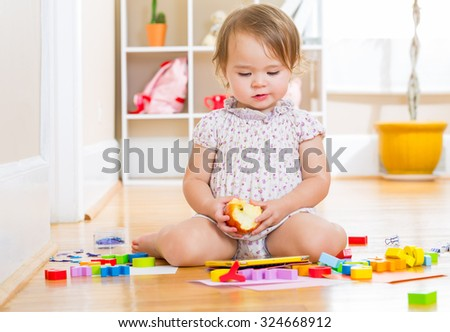 Toddler girl using a tablet computer while eating an apple - stock photo