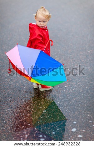 Toddler girl with colorful umbrella on rainy day, beautiful reflection on puddle - stock photo