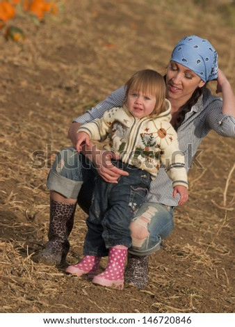 Toddler girl with her mother on the farm.